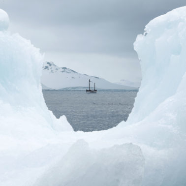 the Alexandra Shackleton, an exact replica of the James Caird which made the original voyage with Shackleton and his crew, is framed by a hollow of iceberg in the foreground
